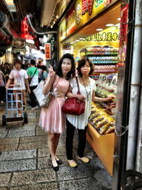 Ladies pose in front of sweetmeat stall