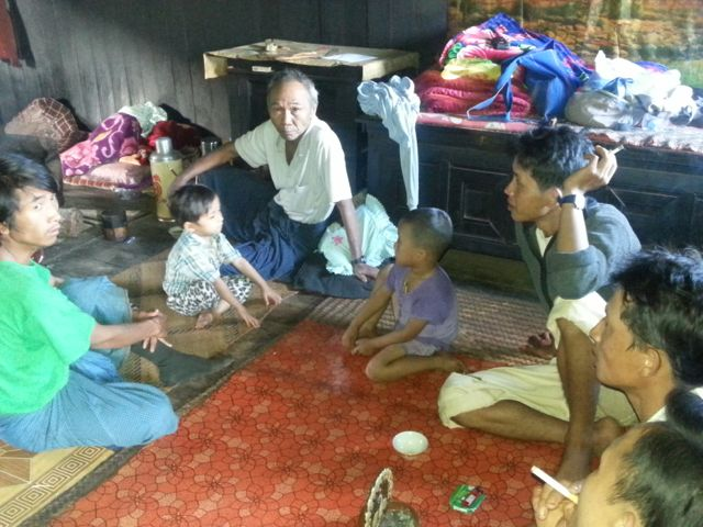 Amaung's father sits with his family in the main room