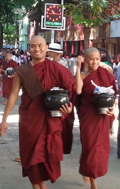 Happy monks carrying their gifts - toothpaste, money as well as food