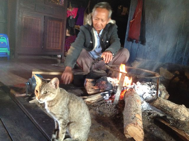 Amaung's father roasting tea on the fire, top cat looks on