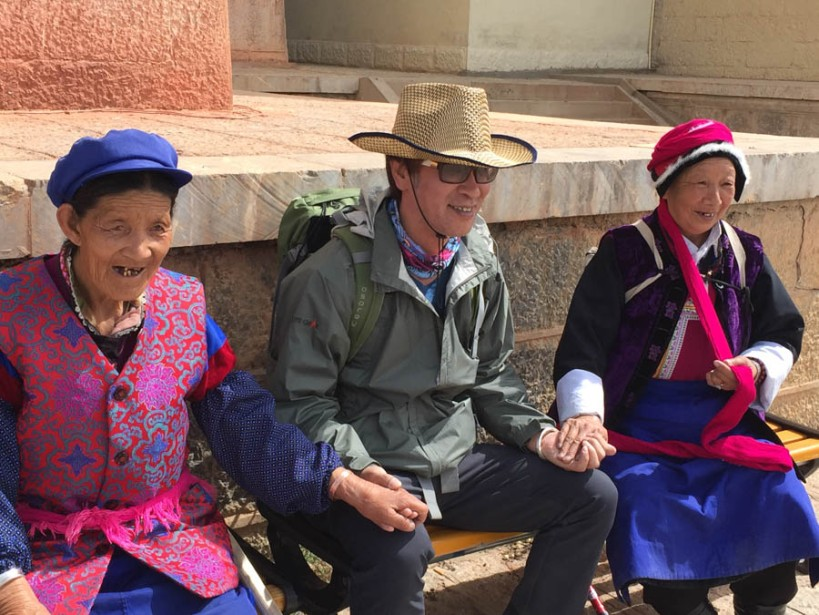 Two Tibetan ladies pose with a Chinese tourist at the monastery