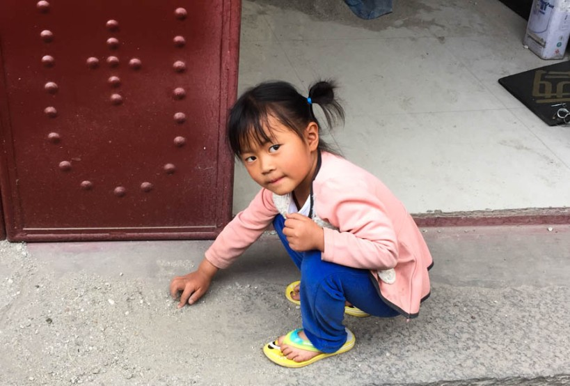 Little girl playing with sand in Xizhou