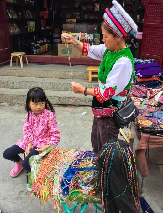 Bai woman doing hair extensions in Xizhou