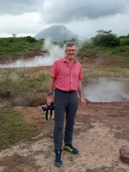 Ross in fornt of one of the bubbling hot-spots with volcano in background